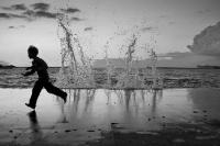 Мальчик бежит вдоль набережной