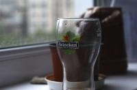 Стеклянный стакан Хайнекен на подоконнике